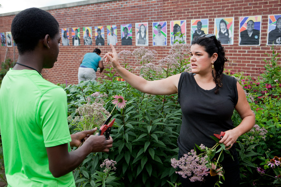 Rebecca Lemos-Otero (right), co-founder and co-executive director of City Blossoms, helps Erwin Tcheliebou, 15, pick flowers to sell at the farmers market. Behind her is a wall featuring the painted portraits of Eastern Senior High students who have worked in the garden. Lydia Thompson/NPR