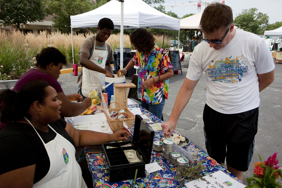 Roshawn Little (left) invites customer Nate Kohring to try the herbed salt with bread at the Aya farmers market on Saturday. Lydia Thompson/NPR