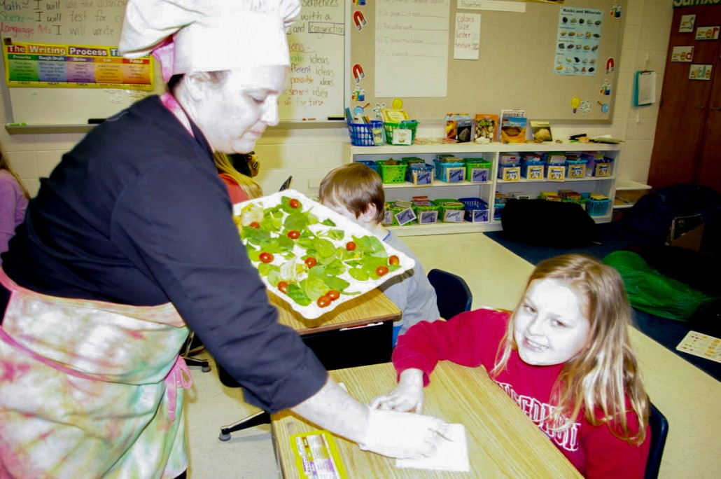 Taher chef Irene Pawlisch hands out a healthy snack to Wilson Elementary third grader Andrea Riesen on Thursday during a presentation about healthy eating at the school